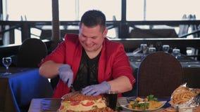En man klipper en enorm hamburgare med en kniv lager videofilmer