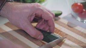 En man klipper grönt ogrutsy med en kniv på ett delat bräde, för förberedelsen av grönsaksallad lager videofilmer