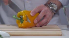 En man klipper en gul peppar med en kniv på ett delat bräde lager videofilmer