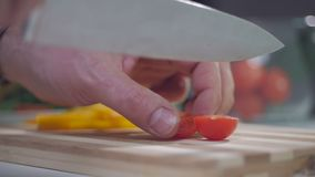 En man klipper en körsbärsröd tomat med en kniv på ett delat bräde lager videofilmer