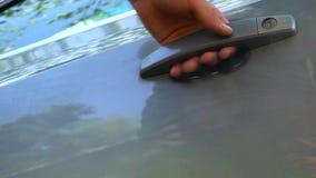 En man kommer till bilen, öppnar dörren med en tangent lager videofilmer