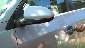 En man kommer ut ur bilen lager videofilmer