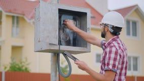 En man kontrollerar elektriciteten för meterläsning i stugan royaltyfria foton