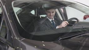 En man kontrollerar inre av medlet Auto affär, bilförsäljning, teknologi och folkbegrepp - lycklig man med bilen stock video