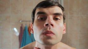 En man kontrollerar kvaliteten av rakningen Undersöker hans framsida i spegeln lager videofilmer