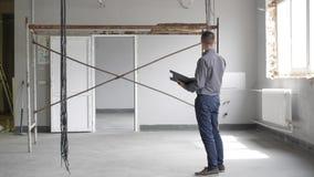 En man kontrollerar reparation inomhus stock video