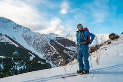 En man kopplas in in skidar turnera på splitboarding Soluppgång i bergen royaltyfria foton
