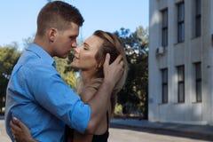 En man kramar en flicka och önskar att kyssa, fingrar i hennes hår, rätar ut hennes hår Stort planera Parkyssar på gatan passion royaltyfri bild