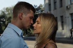 En man kramar en flicka och önskar att kyssa Närbild Parkyssar på gatan passion och dragning arkivfoto