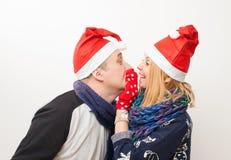 En man kysser en flicka i ett rött lock på vit bakgrund Royaltyfri Foto