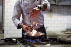 En man lagar mat att laga mat djupa stekpannor i en kökbrand Arkivbilder