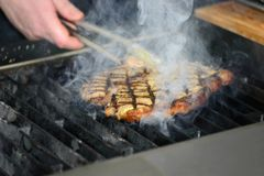 En man lagar mat en biff på gallret mycket rök Arkivfoto