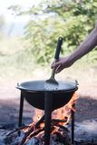 En man lagar mat på brand på naturen arkivfoto