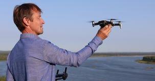 En man lanserar quadcopter Flyga surret över floden och skogen på en solig dag stock video