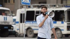 En man ler och talar glatt i en megafon eller en högtalare på ett möte stock video