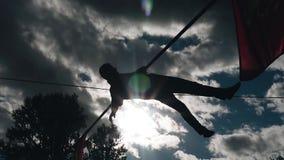 En man ligger med en pol på en kabel ovanför jordningen mot himlen Kall l?ngd i fot r?knat Ilskna blicken f?r sol` s arkivfilmer