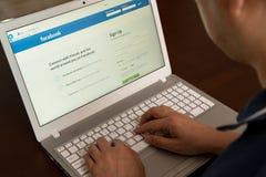 En man loggas in i Facebook med en bärbar dator arkivbild