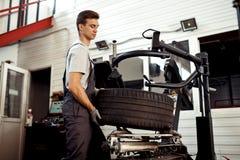 En man lyfter ett gummihjul medan på arbete arkivbild