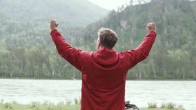 En man lyfter lyckligt upp hans händer på slutet av en svår fotvandra rutt stock video