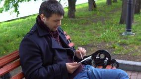 En man lyssnar till musik och arbetar på en minnestavla i parkera arkivfilmer