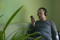 En man lyssnar till musik på telefonen arkivbild