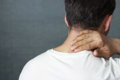 En man masserar en öm hals, närbilden, bakre sikt arkivbild