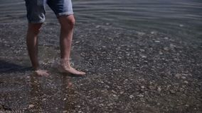 En man med att gå för kal fot går till stranden stock video