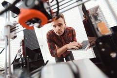 En man med en bärbar dator i hans händer kontrollerar processen av att skriva ut en skrivare 3d skrivaren 3d har skrivavit ut mod Arkivbild