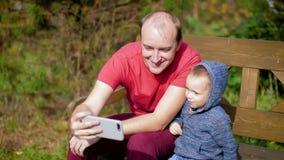 En man med barn som fotograferas på en smartphone som sitter på en bänk En fader tar en selfie med hans lilla son familj stock video
