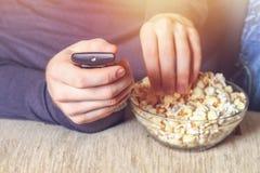 En man med en bunke av popcorn och en fjärrkontroll i hans hand ser TV:N på soffan royaltyfria bilder