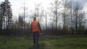 En man med en chainsaw och en signalväst kommer in i skogen lager videofilmer
