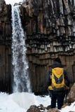 En man med den gula ryggsäcken som bara står på den Svartifoss vattenfallet i Island Lopplivsstilbegrepp royaltyfri bild