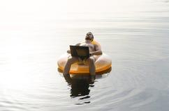 En man med en bärbar dator på en uppblåsbar cirkel i vattnet på solnedgången Arkivfoto