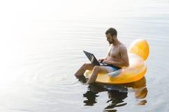 En man med en bärbar dator på en uppblåsbar cirkel i vattnet på solnedgången Arkivbilder
