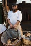 En man med en korg med bröd arkivfoton