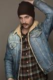 En man med en mustasch i jeans klår upp Fotografering för Bildbyråer