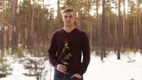 En man med en röd ros i vinterforestSlowrörelsen arkivfilmer
