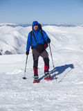 En man med en ryggsäck och snöskor Royaltyfria Bilder