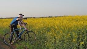 En man med ett barn på en cykel Farsa och dotter i natur Farsan förklarar till barnet sportfamilj lager videofilmer