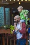 En man med ett barn på hans skuldror som går ner gatan royaltyfri fotografi