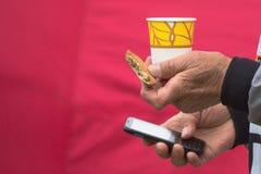 En man med ett exponeringsglas av te, kakor och en telefon på en röd bakgrund royaltyfri foto