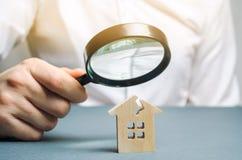 En man med ett förstoringsglas ser ett hus med en spricka Risker för hem och för försäkring för skadebedömning arkivfoto