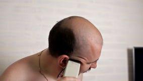 En man med ett mustaschrakninghår på hans huvud med en rakapparat i badrummet hemma Ta omsorg av ditt arkivfilmer