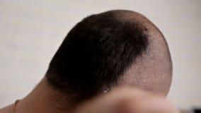 En man med ett mustaschrakninghår på hans huvud med en rakapparat i badrummet hemma Ta omsorg av ditt stock video