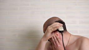 En man med ett mustaschrakninghår på hans huvud med en rakapparat i badrummet hemma Ta omsorg av ditt lager videofilmer