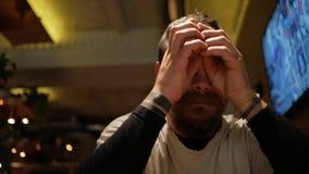 En man med ett skägg gnider hans ögon lager videofilmer