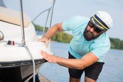 En man med ett skägg kontrollerar hans yacht arkivfoto