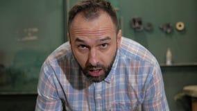 En man med ett skägg lyfter hans huvud lager videofilmer