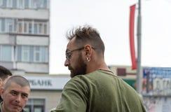 En man med ett skägg och ett örhänge i hans öra talar med en annan man på en stadsdagberöm arkivbilder