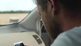 En man med ett skägg ser in i telefonen, medan sitta framtill platsen av en bil 4K video 4K arkivfilmer